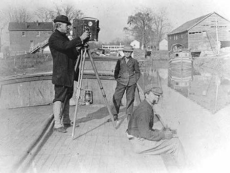 A man in a hat stands behind an early movie camera, balanced on a tripod on a canal boat.