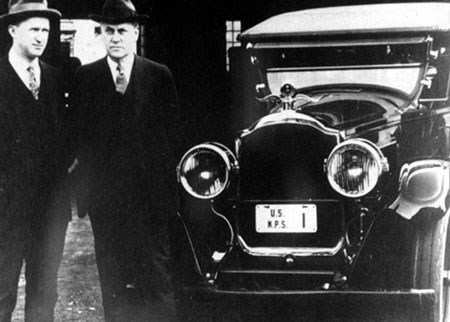 Two men in suits, ties, and brimmed hats stand near the front of a 1920s car.