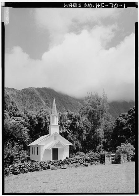 The sharp white spire of a small church stands out from dense foliage and low stone walls.