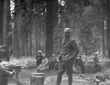 Stephen Mather, in uniform with high boots, buttoned jacket, and hands in pockets, stands amid onlookers in a forest.