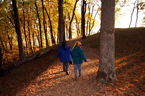 Two young hikers on a leaf-covered hillside trail with autumn trees