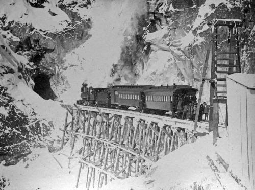 Train on a snowy railroad bridge approaches a tunnel in the side of a mountain.