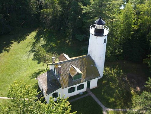 High angle view from above a white lighthouse and keeper's quarters, surrounded by trees and grass