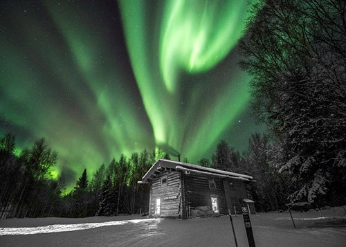 Green lights swirl in the night sky over a wooden cabin in snowy woods.