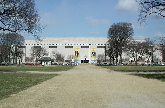 View of the National Museum of American History following 13th Street, with elms arising in the foreground of the building on either side of the broad walkway leading to its doors.