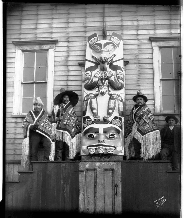 Four men, wrapped in blankets, sit on either side of a totem pole.