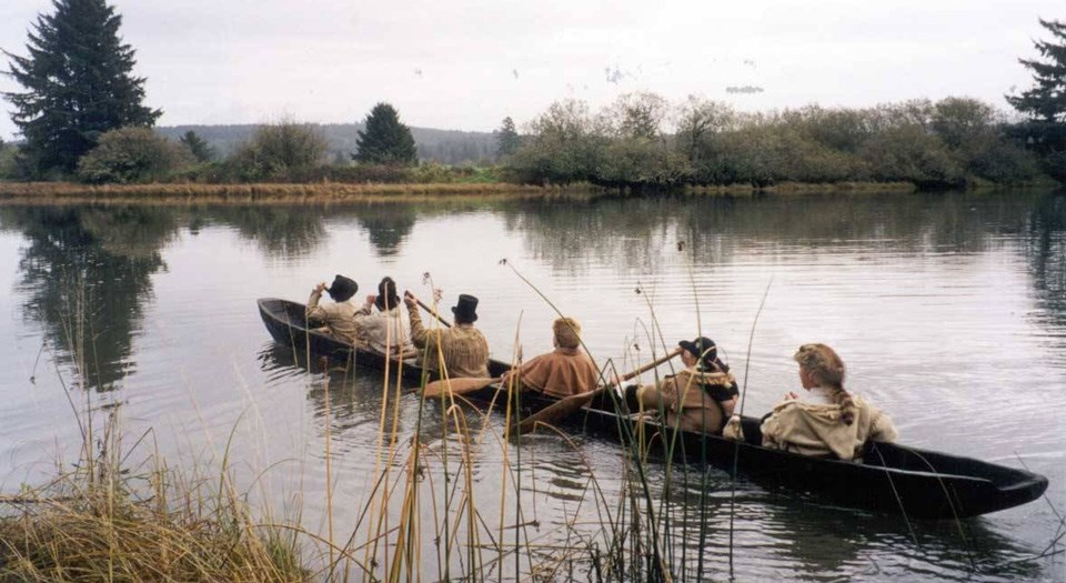 Six people paddle a long canoe through still water.