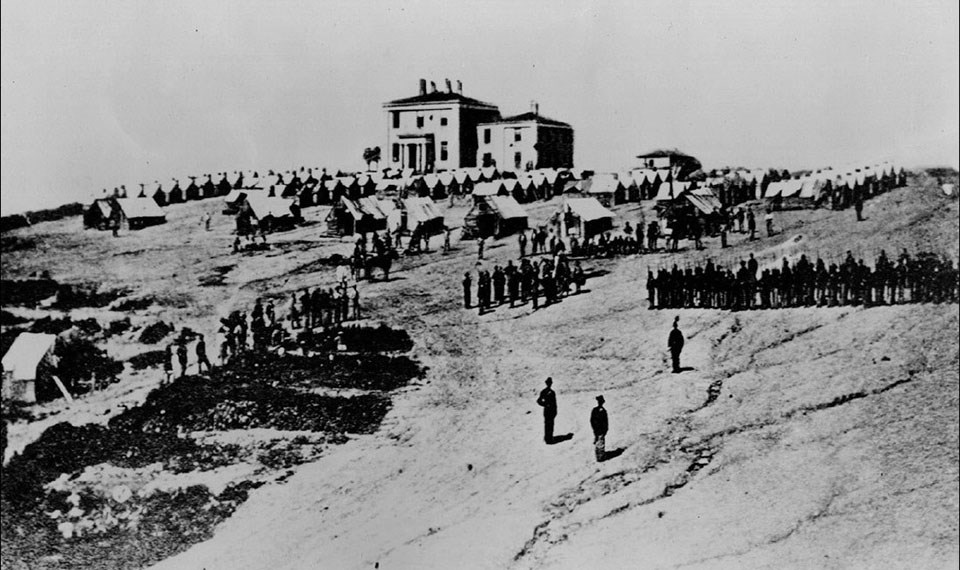 Troops stationed at the armory superintendent's house in 1862, showing a bare and compacted earth.