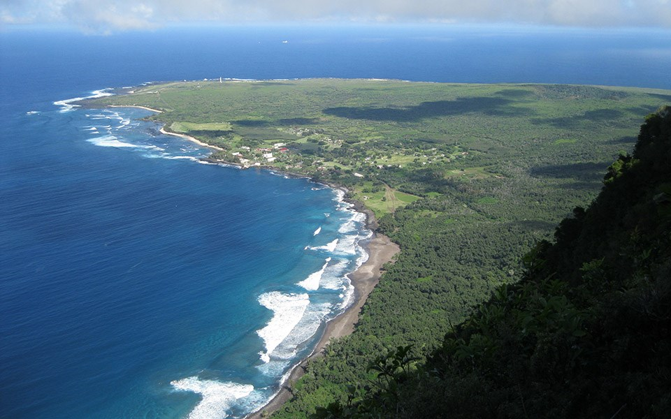 View from the Pali Trail to Kalaupapa Peninsula, level and green surrounded by bright water.
