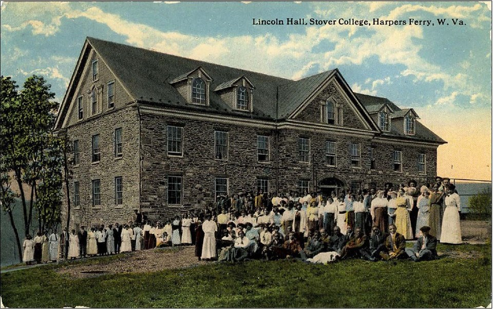 A tinted postcard shows a group of students and instructors, many African American, in front of the large stone Lincoln Hall at Storer College