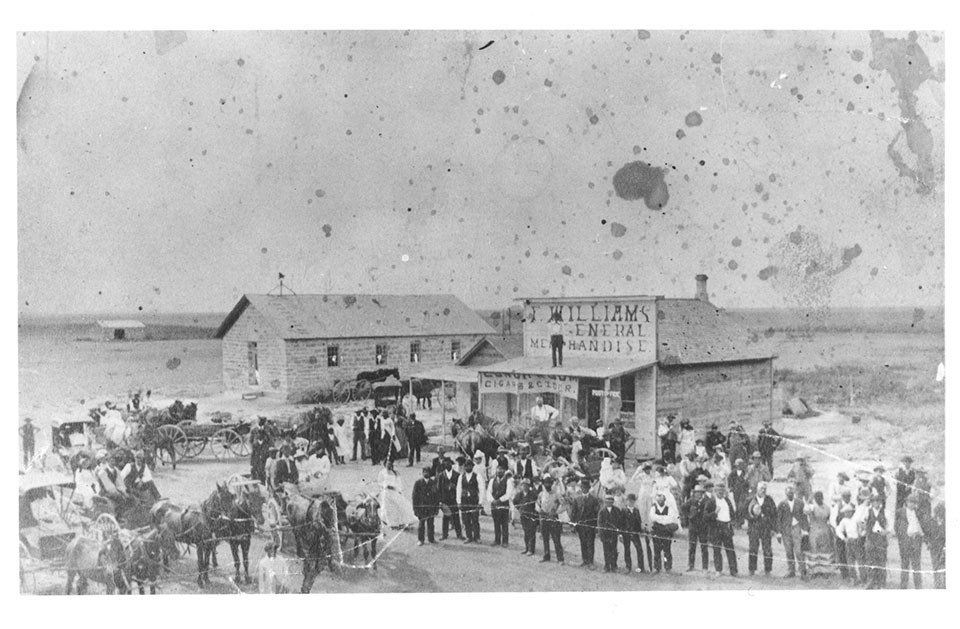 Historic photo of the town of Nicodemus with many people and horses in front of a few structures.