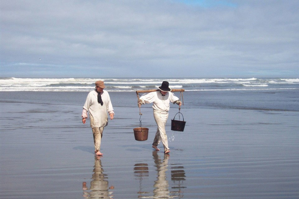 Two people dressed in period-era white clothing walk along the ocean shoreline, one carrying two buckets.