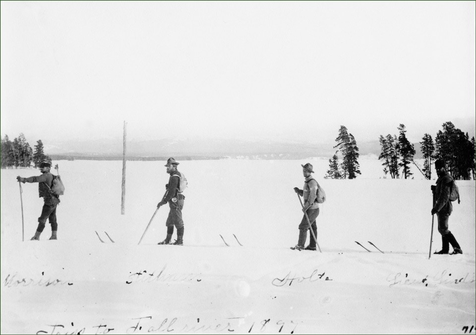 Four men on skis cross an open area of snow in 1897.