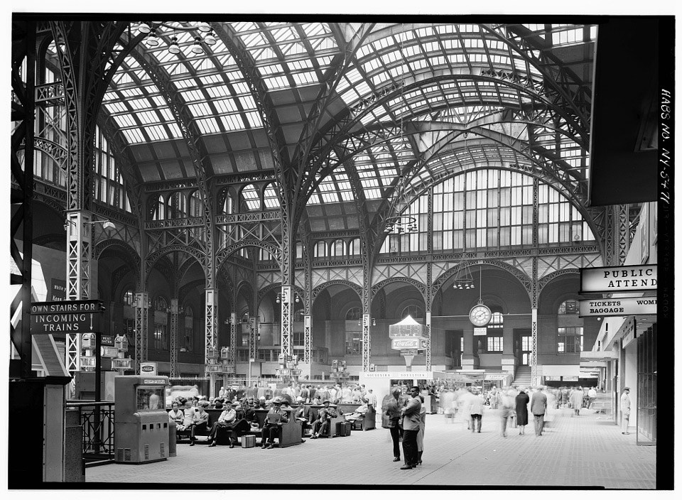Passengers gather in the expansive concourse of a train station under an arching glass and metal ceiling.