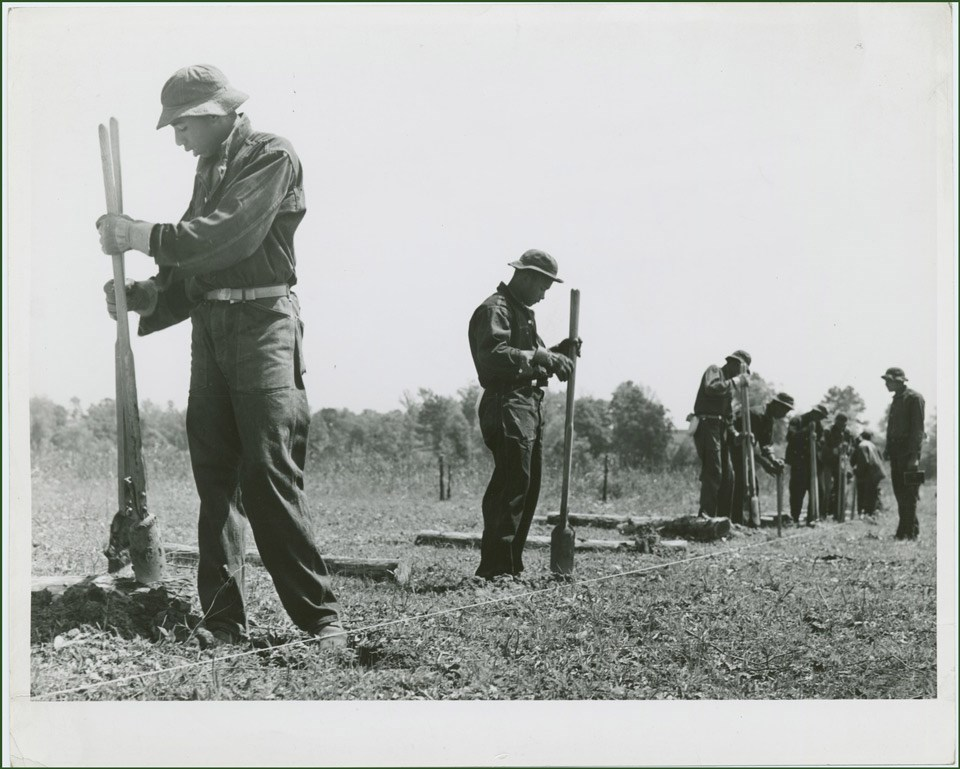 A row of young men in work uniforms dig post holes for a fence.
