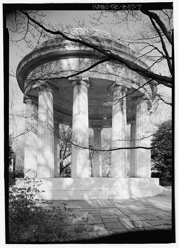 View was photographed looking up at the structure from the turf. Tree branches with early spring buds cast a shadow on the white marble of the memorial.