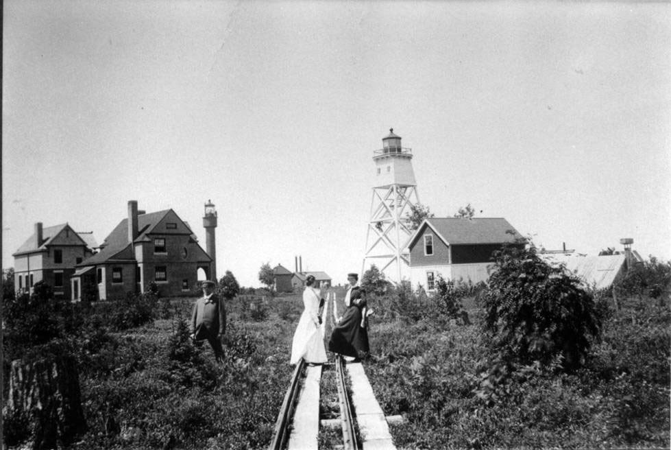 Three people stand on tram tracks beside the buildings and a lighthouse