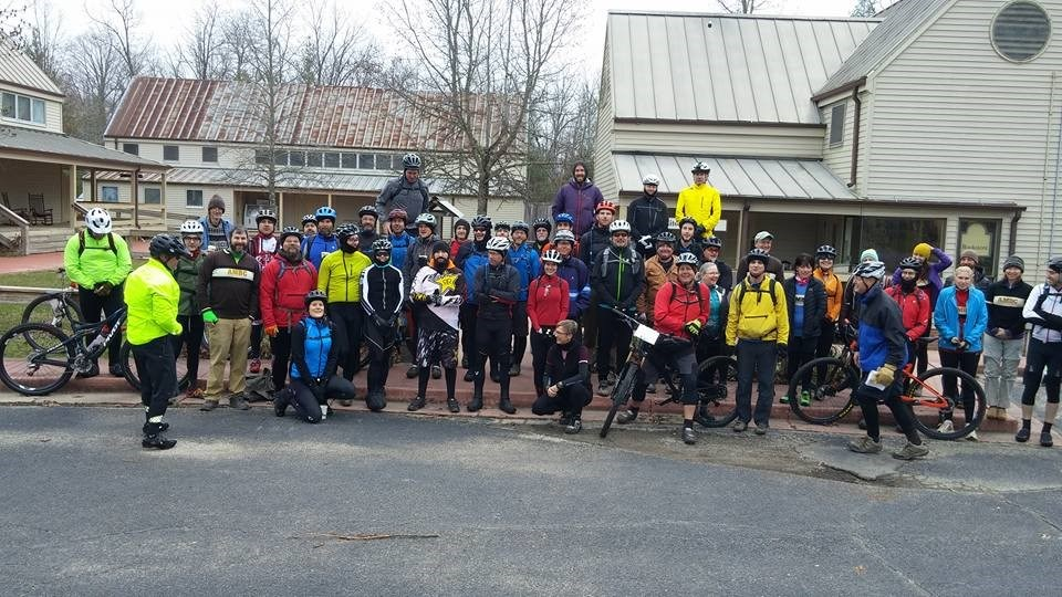 A large group of cyclists in helmets, bright clothes pose in front of several barn-like structures