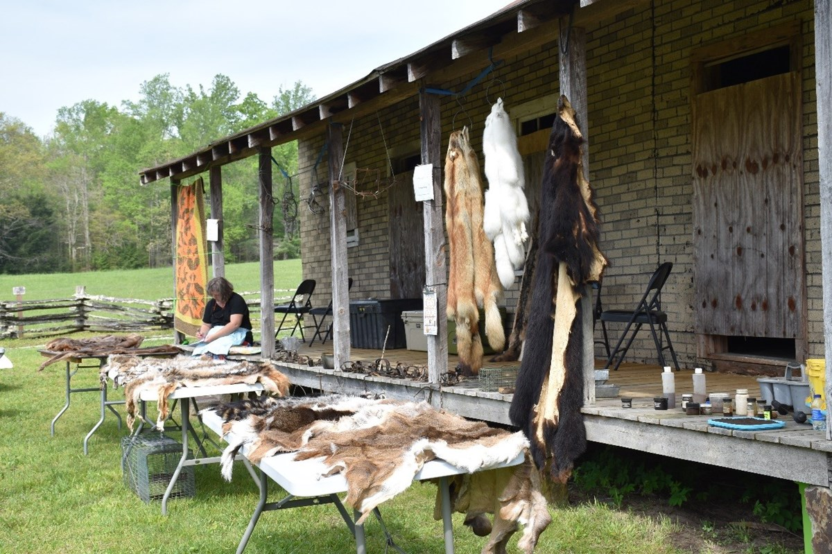 Animal hides are displayed on tables in front of the long wooden porch of a rural cabin