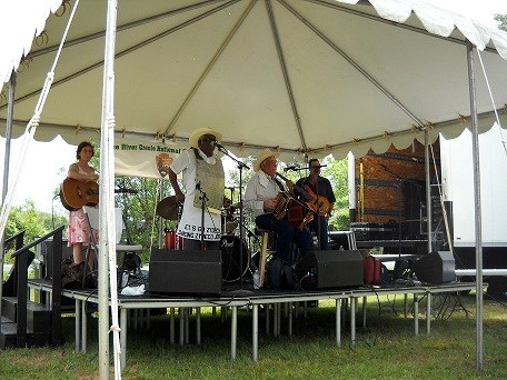 Goldman Thibodeaux and the Lawtell Playboys perform on stage under a tent