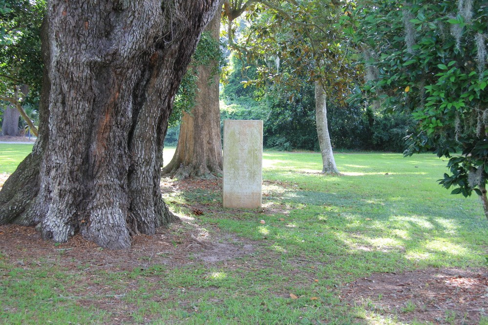 A rectangular memorial, light colored with green lichen, stands in grass under towering trees.