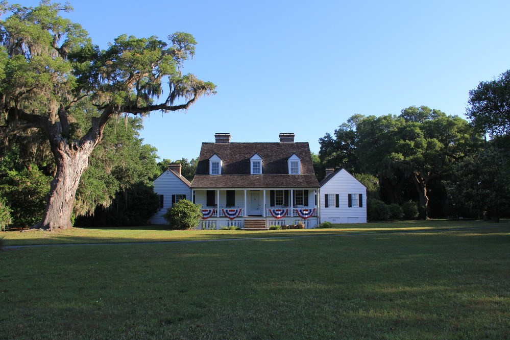 Snee Farm is a two-story white house surrounded by open  lawn and large, leafy trees, with patriotic bunting on the front porch.