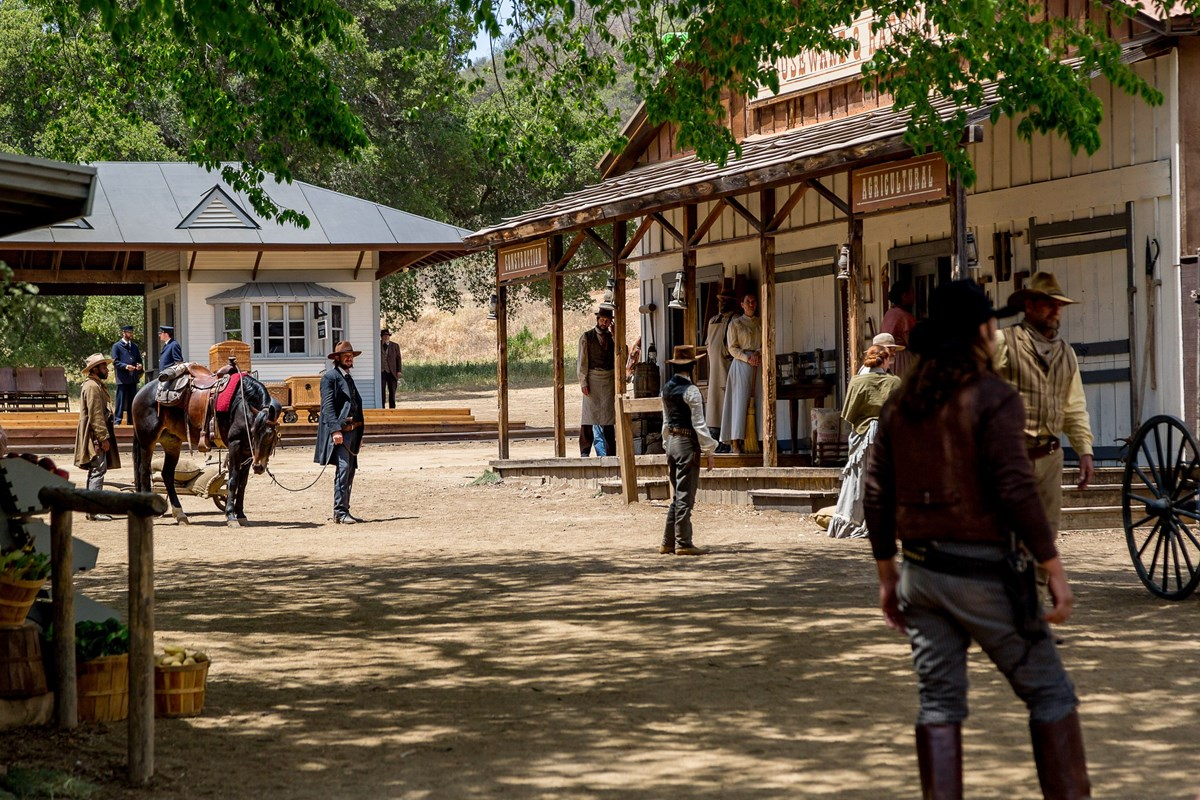 People in western period clothing in the dappled shade in front of a store front.