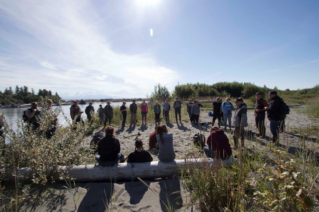 A group stands in a circle on a beach with low vegetation