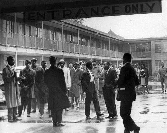 A group of men in overcoats gather in a rainy courtyard of a two-story motel.