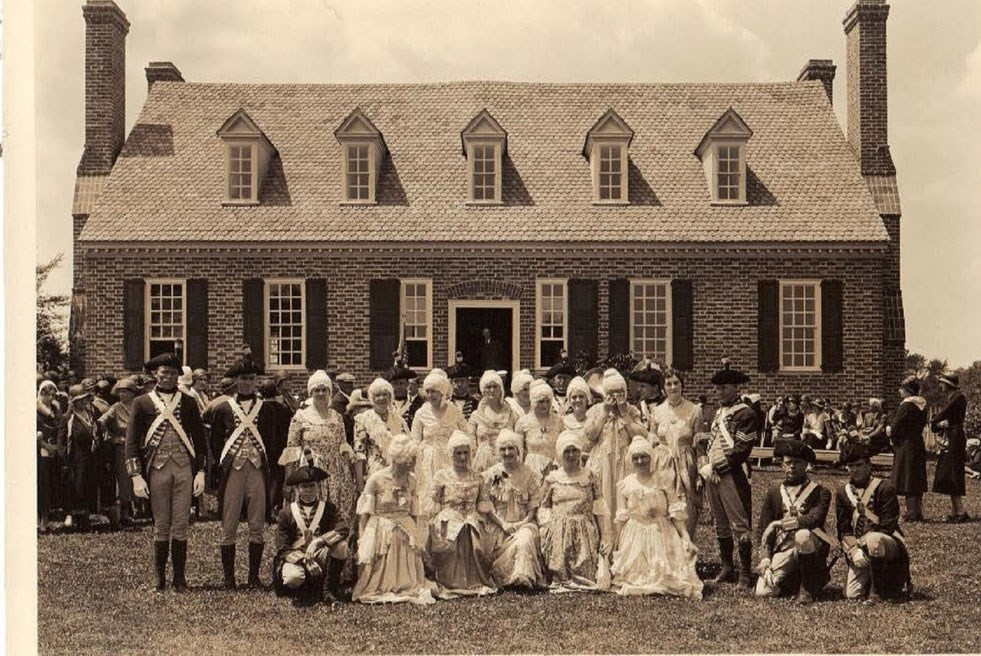 People in colonial costume stand in two rows in front of a brick house.