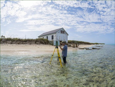 A man stands in knee-deep water near a sandy beach, using a laser scanning device on a tripod.