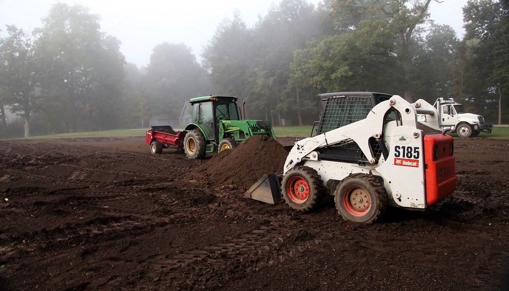 A heap of fine, dark topsoil stands in the middle of an expanse of dirt, with a backhoe and a tractor.