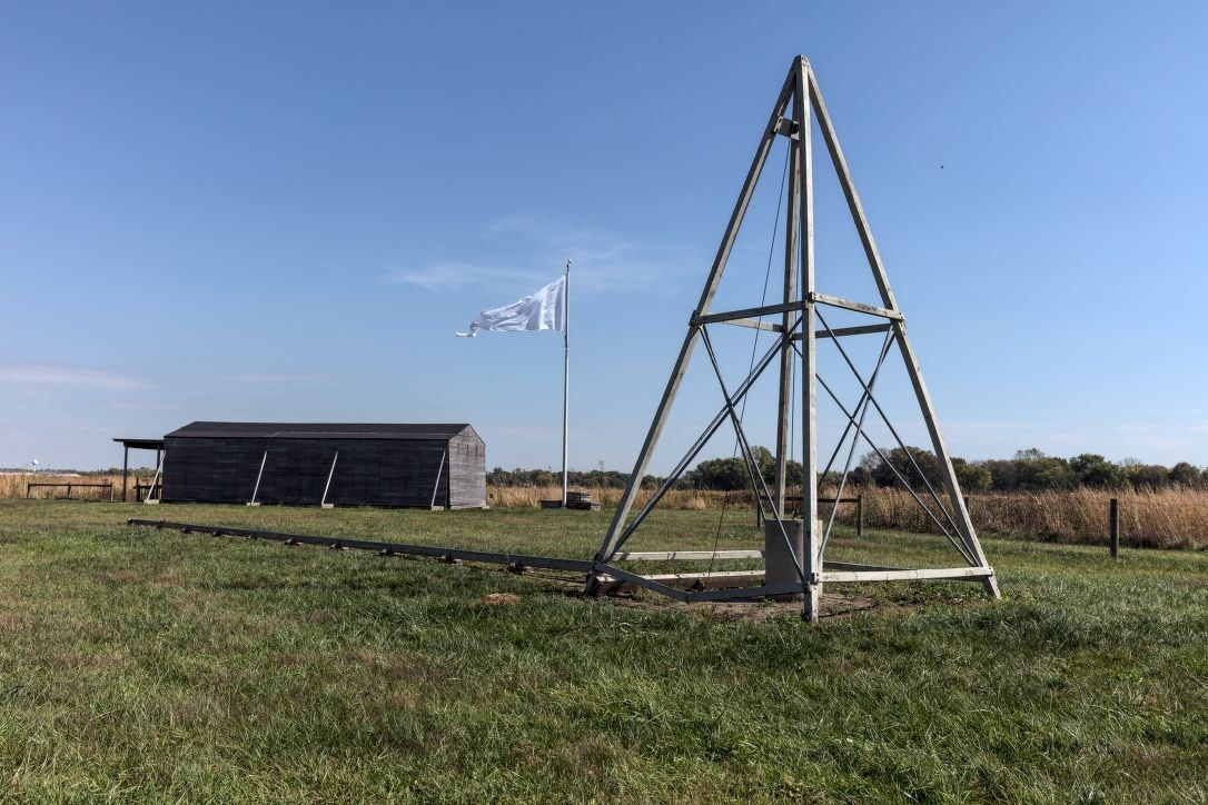 Pyramid shaped catapult in an open field, with a wooden hanger and white flag in the background