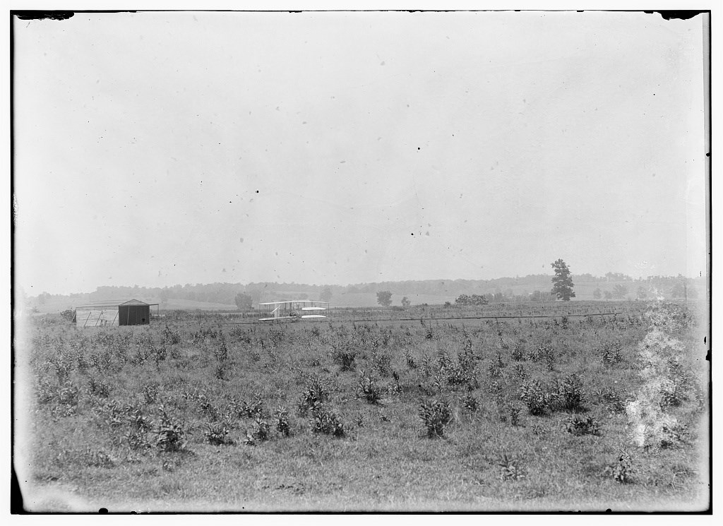 Long-range view of machine on launching track, showing hangar nearby and hummocky ground of former swamp at Huffman Prairie, Dayton, Ohio