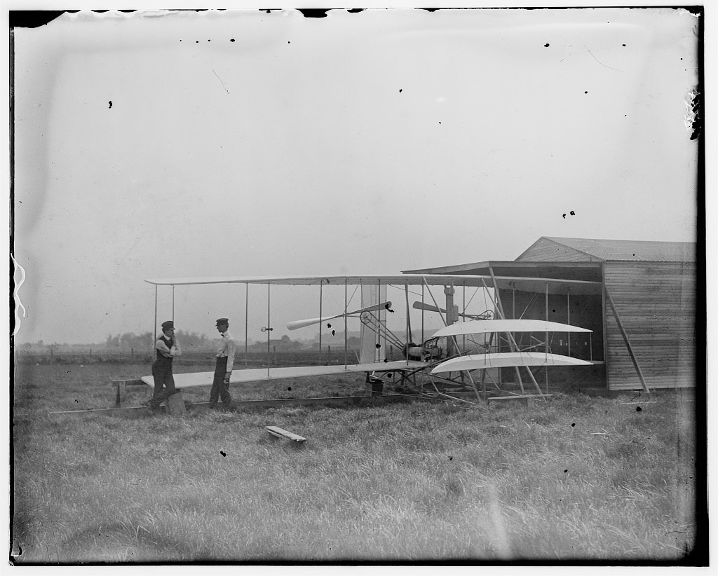 Wilbur and Orville Wright with their second powered machine beside a hanger; Huffman Prairie, Dayton, Ohio