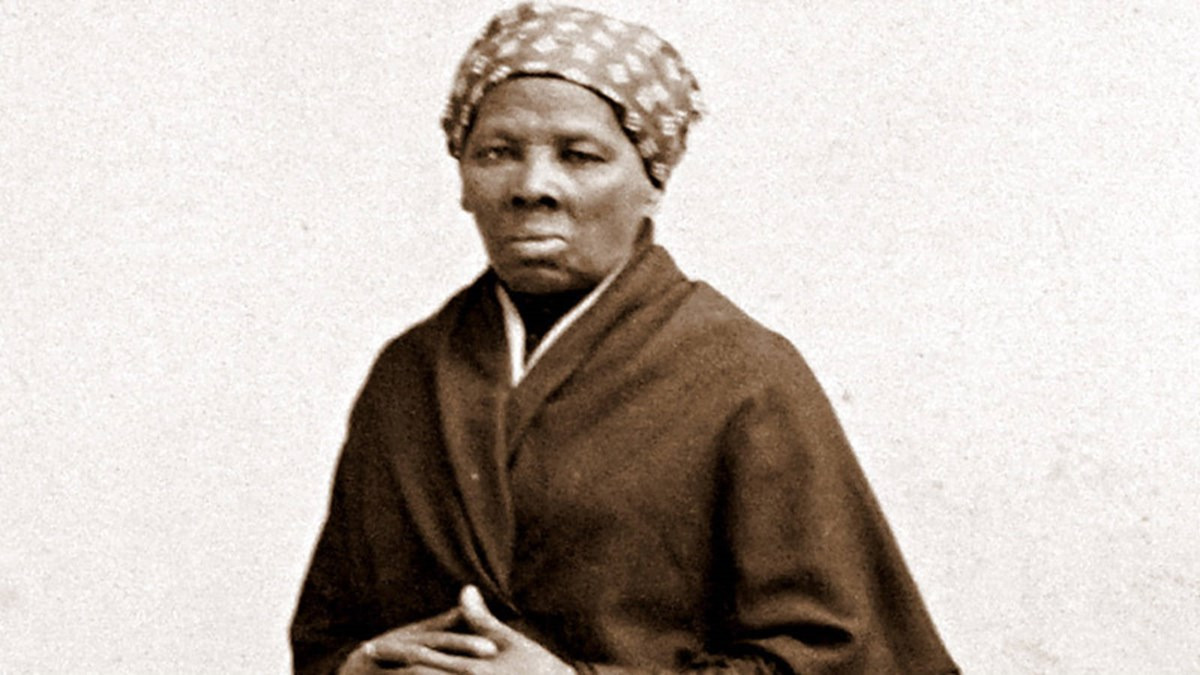 Portrait of an African American woman with a headscarf and cloak, her hands folded in front of her.