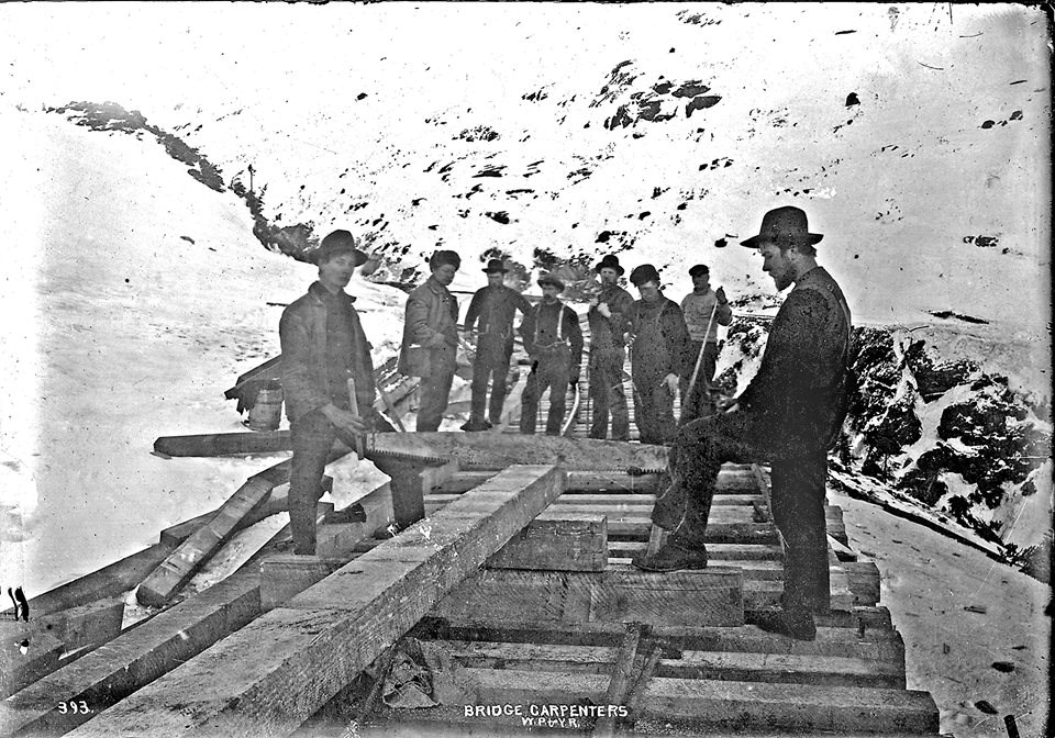 A group of 8 men pause on a partially-completed railway through a winter landscape.