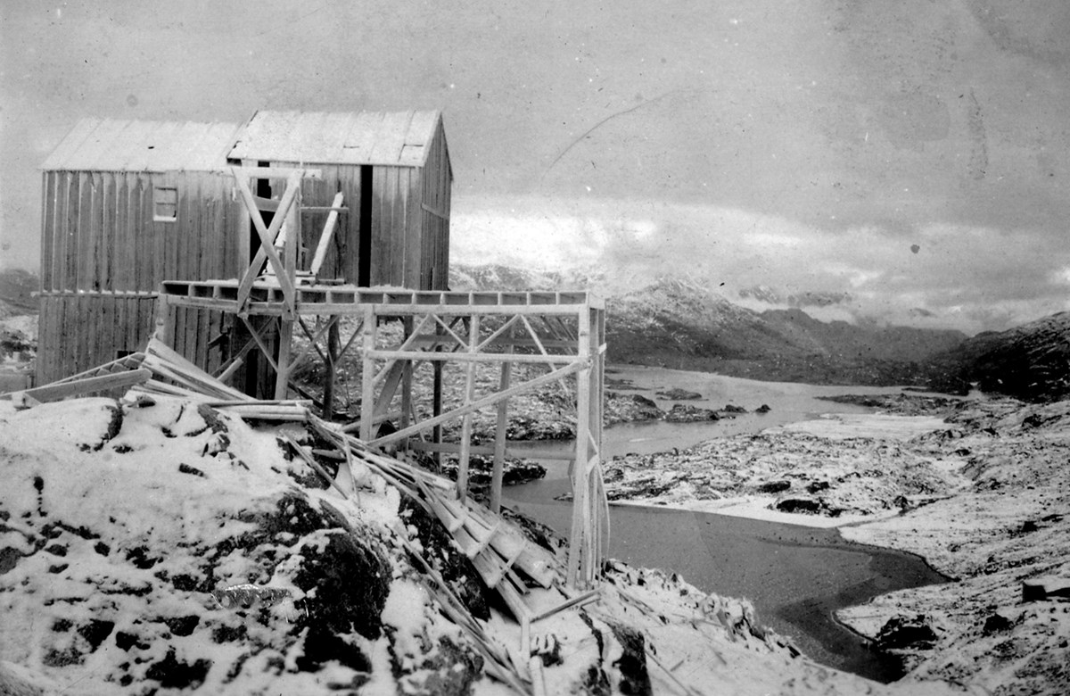 A partially collapsed wooden structure supported by beams on the edge of a snowy hillside, overlooking a lake.