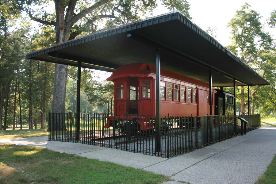 A red engine and black train coach are under a covered pavilion, surrounded by trees, sidewalk, and grass