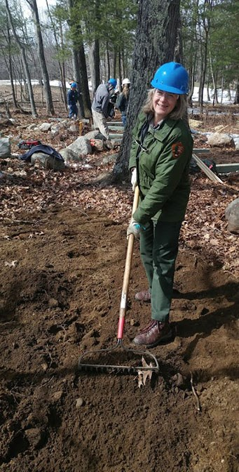 A woman in NPS uniform, hardhat, and gloves pulls a rake through dark soil