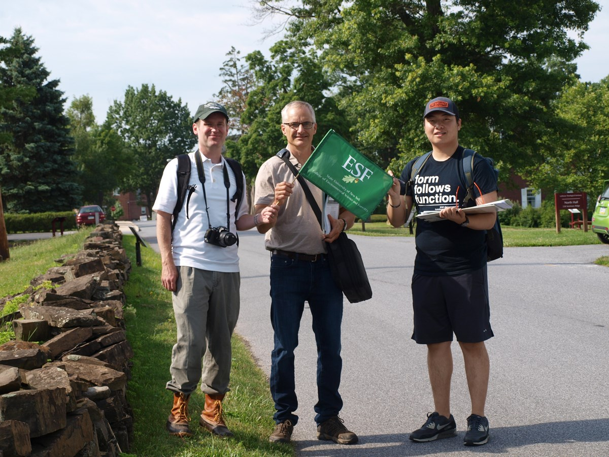 "Three men, one with a camera and one with an ""ESF"" flag, beside a low stone wall."
