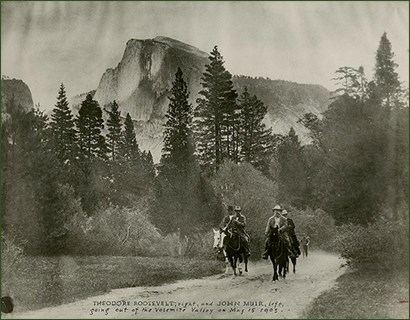 Historic image of four men on horses riding a trail, mountains and trees in the background.
