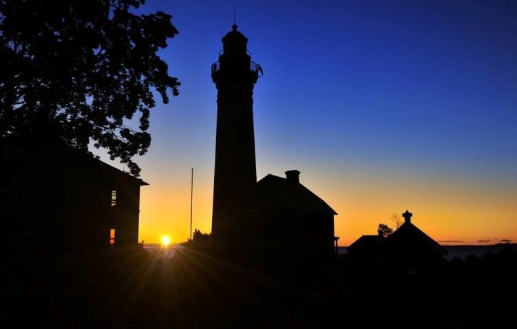 Sunrise begins behind the silhouette of a lighthouse