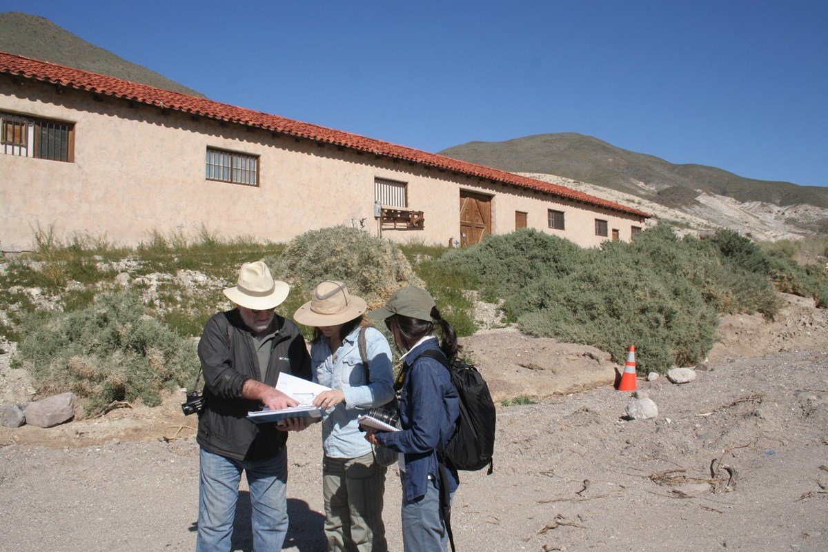 A group of three people with hats and cameras look at a cultural landscape report to assess condition at Death Valley.