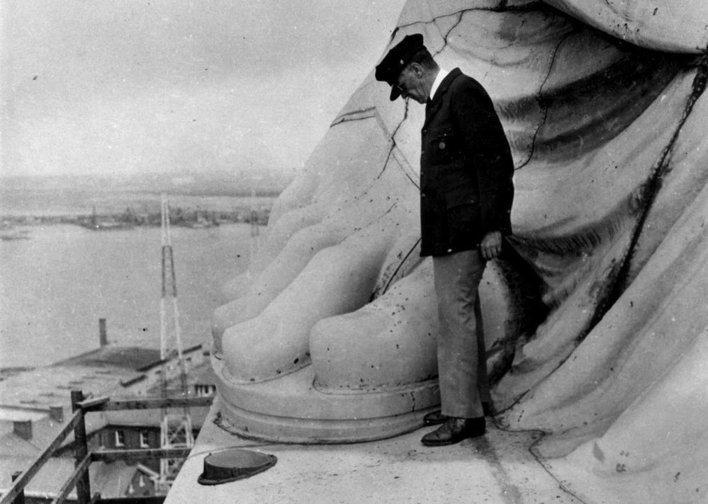A superintendent with a cap and jacket stands at the base of a a statue beside a large carved foot, overlooking the harbor.