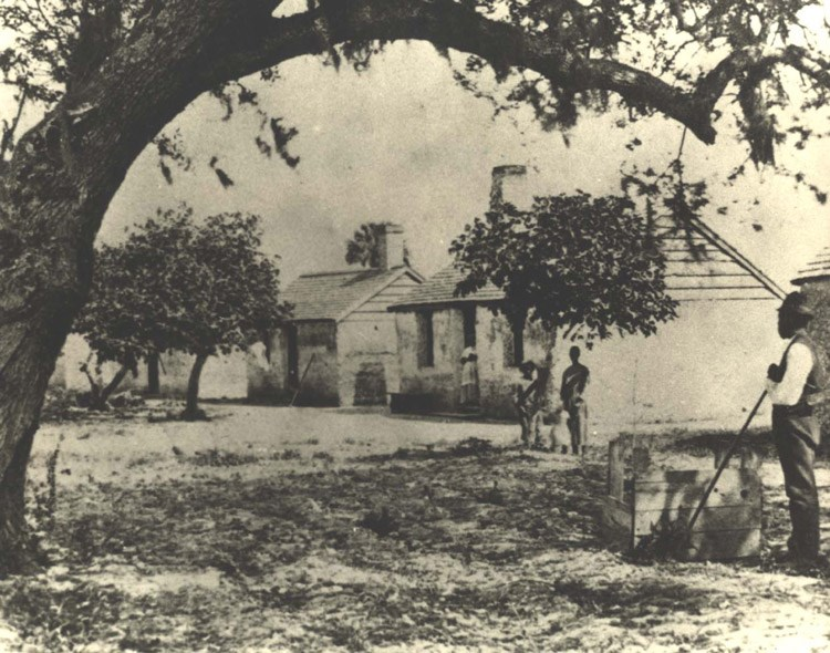 Historic image of an African American man standing beside a square well under a tree, near a row of small symmetrical cabins.