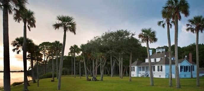 A scattering of palmetto trees grow on the lawn in front of a white plantation house, overlooking a body of water.