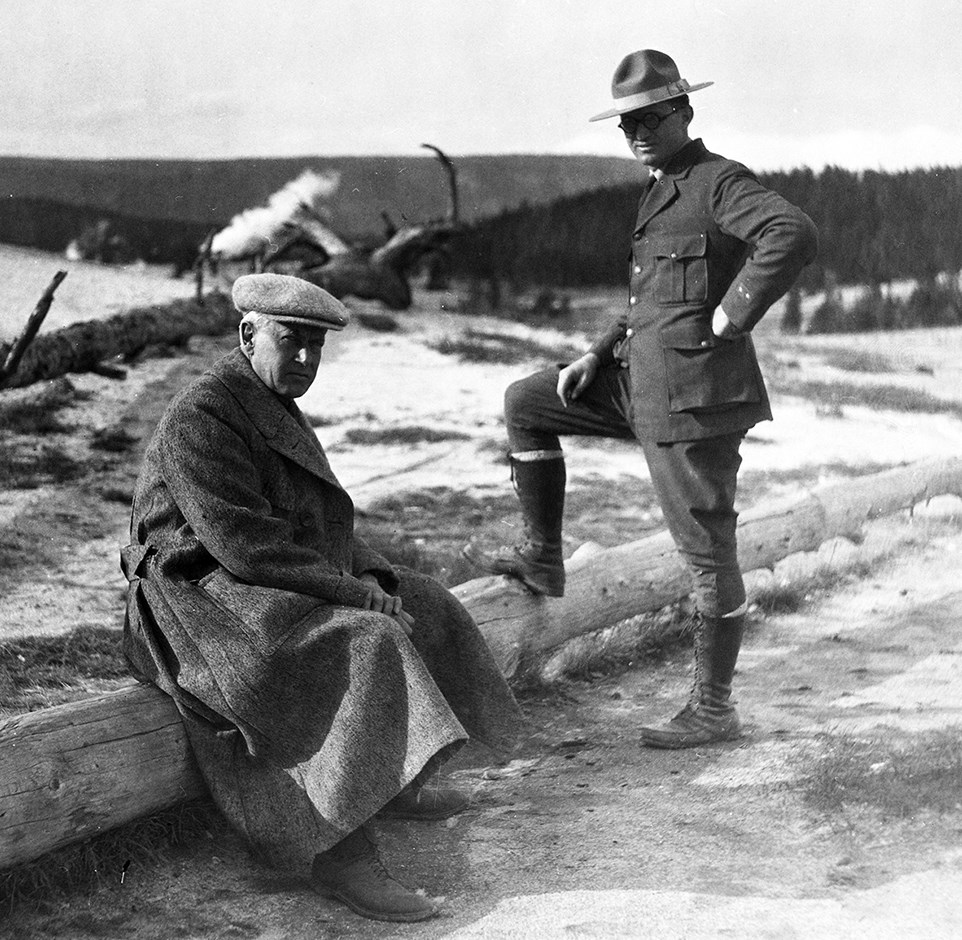 A man in NPS uniform stands with one foot on a fallen log, beside a seated man in a long coat and cap.