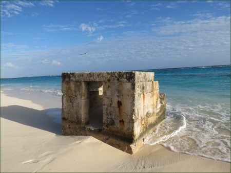 A square concrete bunker with a door on one side is surrounded by a sandy beach and bright ocean water.