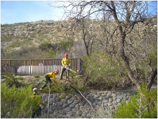 Three firefighters work near a stone wall and propane tank in a desert environment.